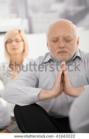 Portrait of meditating senior businessman with hands put together, eyes closed, wearing formal dress in office.? - stock photo