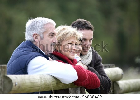 Portrait of men and women leaning on a wooden barrier in the countryside - stock photo