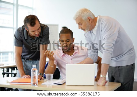 Portrait of men in front of a laptop computer - stock photo