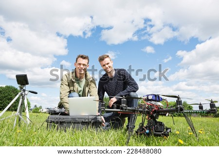 Portrait of men using laptop next to UAV octocopter and tripod against cloudy sky - stock photo
