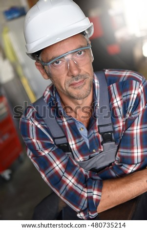 Portrait of metalworker with security helmet in workshop