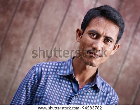 Portrait of mid adult asian man staring at camera against brown wall. Copy space