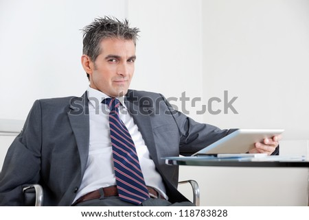 Portrait of mid adult businessman using digital tablet at desk in office - stock photo