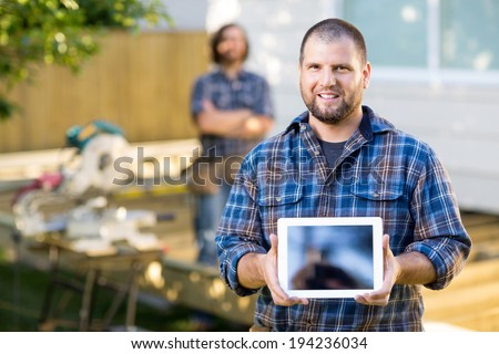Portrait of mid adult carpenter displaying digital tablet with coworker in background at construction site - stock photo