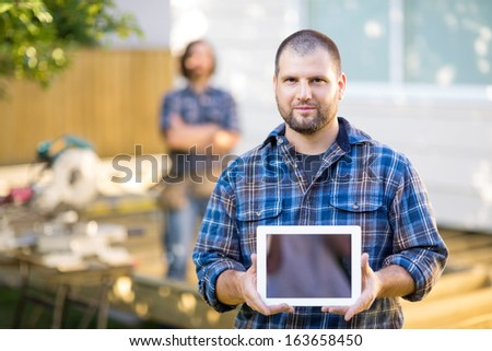 Portrait of mid adult confident carpenter displaying digital tablet with coworker in background at construction site - stock photo