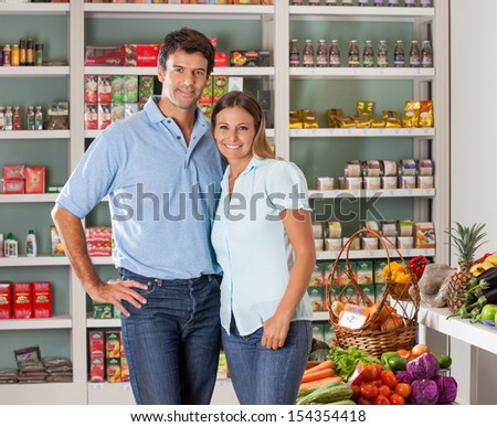 Portrait of mid adult couple standing in grocery store - stock photo