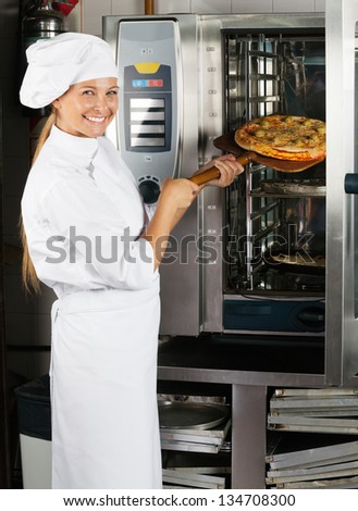 Portrait of mid adult female chef placing pizza in oven at commercial kitchen - stock photo