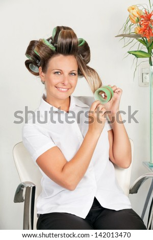 Portrait of mid adult female client removing curlers at parlor - stock photo