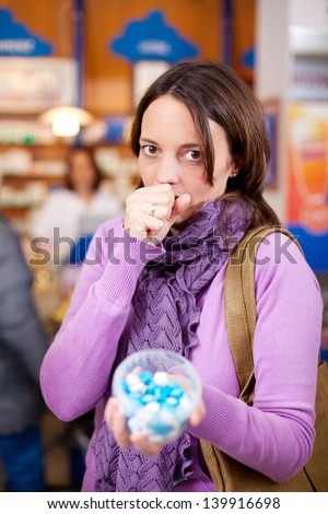 Portrait of mid adult female customer holding container filled with medicines at pharmacy - stock photo
