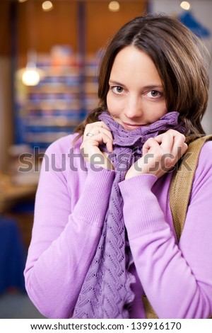 Portrait of mid adult female customer in sweater and scarf shivering at pharmacy - stock photo