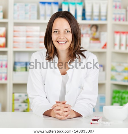 Portrait of mid adult female pharmacist with hands clasped leaning on pharmacy counter