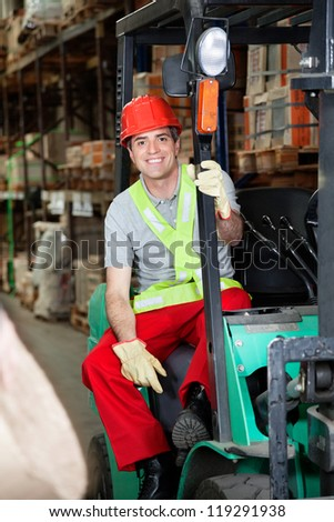 Portrait of mid adult foreman sitting on forklift at warehouse