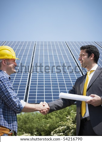 Portrait of mid adult italian male engineer holding blueprints and shaking hands to manual worker in solar power station. Vertical shape, side view. Copy space - stock photo