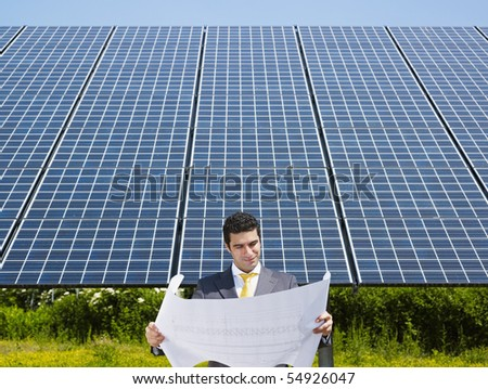 Portrait of mid adult italian male engineer reading blueprints in solar power station and smiling. Horizontal shape, front view. Copy space