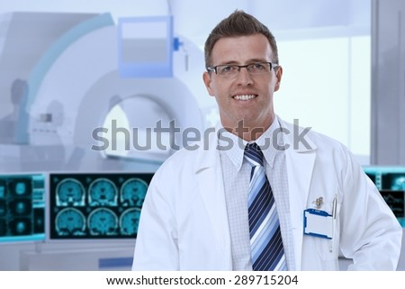 Portrait of mid-adult male doctor in MRI room at hospital, looking at camera, smiling. - stock photo