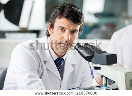 Portrait of mid adult male scientist using microscope in laboratory - stock photo