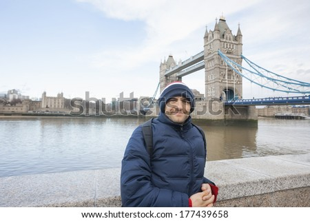 Portrait of mid adult man in warm clothing standing in front of tower bridge; London; UK - stock photo