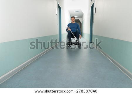 Portrait Of Mid-adult Man Sitting On Wheelchair With Crutches - stock photo
