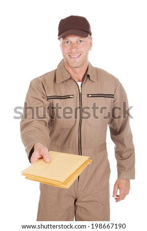 Portrait of mid adult postman giving envelopes over white background - stock photo