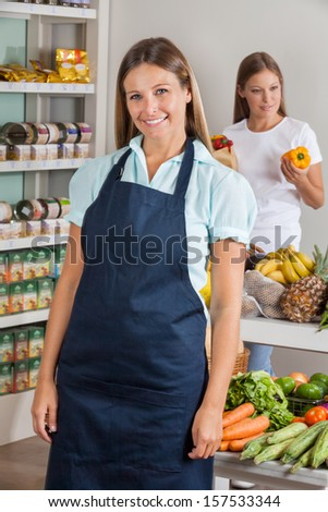 Portrait of mid adult saleswoman with female customer shopping in background at supermarket - stock photo