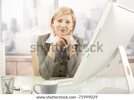 Portrait of mid-adult smiling businesswoman sitting at office desk.? - stock photo