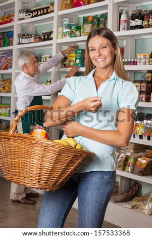 Portrait of mid adult woman holding shopping basket with salesman in background - stock photo