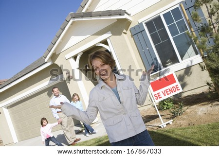 Portrait of mid-adult woman in front of new house
