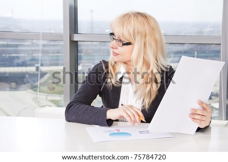 Portrait of mid adult woman sitting at a table in the office against the window and work with documents