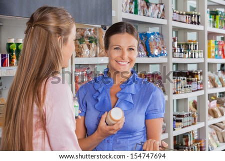 Portrait of mid adult woman with friend shopping in supermarket - stock photo