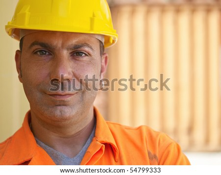 portrait of mid adult worker standing near cargo containers and looking at camera. Horizontal shape, front view, copy space - stock photo
