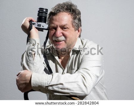 Portrait of middle age and handsome professional photographer  - stock photo