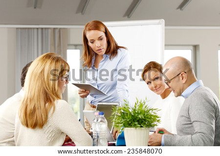 Portrait of middle age business woman holding tablet and presenting her idea to business team while sitting at meeting.  - stock photo