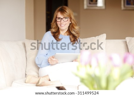 Portrait of middle age business woman sitting at sofa and holding digital tablet in her hands. Mature woman working at home. - stock photo