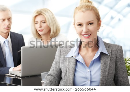 Portrait of middle age business woman standing at business meeting while business people working with laptop at background. Teamwork at office.  - stock photo