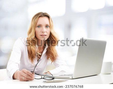 Portrait of middle age business woman with laptop sitting at office and working on project.  - stock photo
