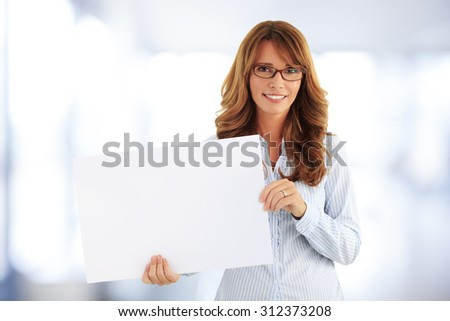 Portrait of middle age businesswoman holding hands blank sign while standing at office.  - stock photo