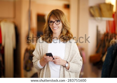 Portrait of middle age businesswoman holding smart phone and texting message while standing in her small store. Small business.  - stock photo
