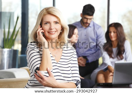 Portrait of middle age businesswoman sitting af office  and making call while her colleagues consulting at background.