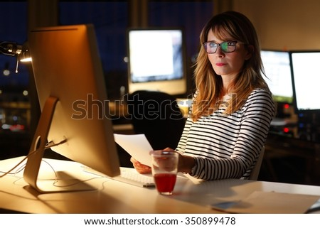 Portrait of middle age businesswoman sitting at office desk and working late in front of computer. Casual professional officer holding in her hands a document and analyzing financial data. - stock photo