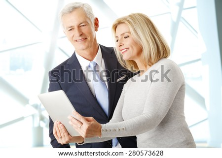 Portrait of middle age businesswoman standing at office and holding hands digital tablet while consulting with senior manager. Teamwork at office.  - stock photo