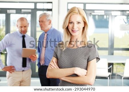 Portrait of middle age businesswoman standing with arms crossed in foreground while business people standing behind her. Business persons using digital tablet and consulting. Teamwork at office.