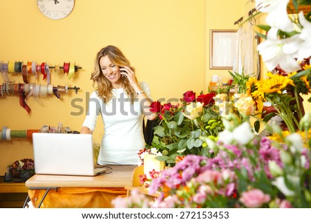 Portrait of middle age florist standing at her flower shop and using her telephone and laptop to take orders for her store.