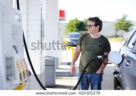 Portrait of middle age man filling gasoline fuel in car  - stock photo