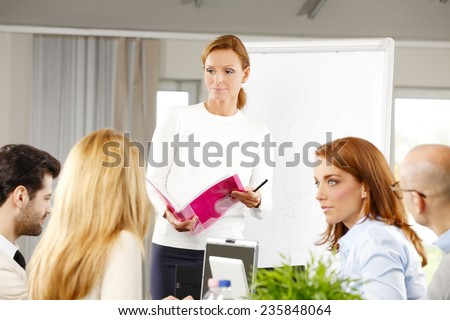 Portrait of middle age sales woman presenting her idea to sales team while they sitting at meeting - stock photo