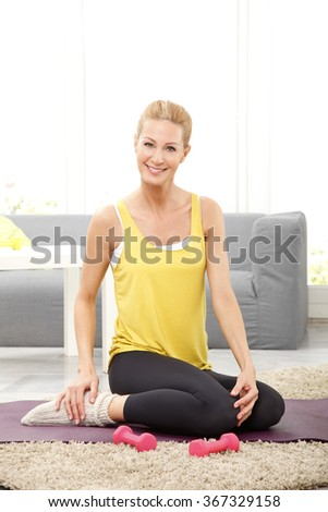 Portrait of middle age sporty woman sitting on yoga mat at home after workout with dumbbells.