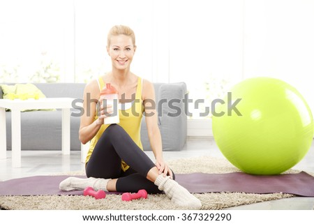 Portrait of middle age woman holding in her hand a shaker while sitting on a yoga mat at home and relaxing after fitness workout.  - stock photo
