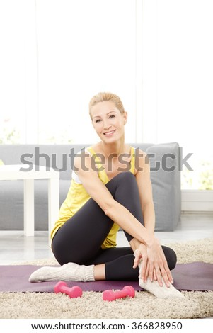 Portrait of middle age woman sitting at home after fitness workout while looking at camera and smiling.