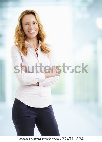 Portrait of middle age woman standing at office. Business people. - stock photo