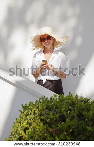 Portrait of middle age woman wearing straw hat and sunglasses while standing in garden at home. Mature female writing email on her smart phone.  - stock photo