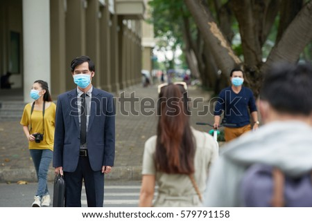 Portrait of middle-aged Asian businessman wearing facial mask in order to protect himself from smog while crossing road with other people